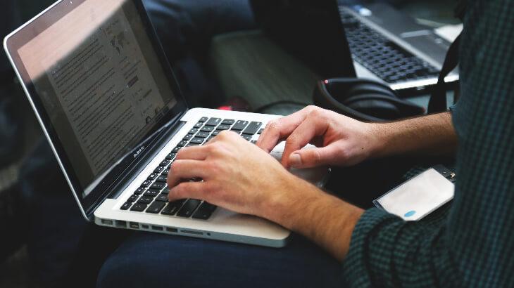 macbookでタイピングをする男性