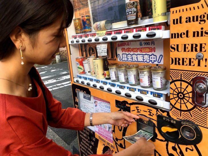 昆虫食自動販売機にお金をいれる写真