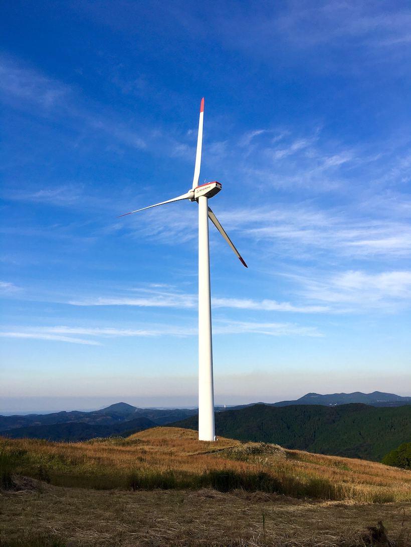 山頂に風力発電機がそびえ立つ