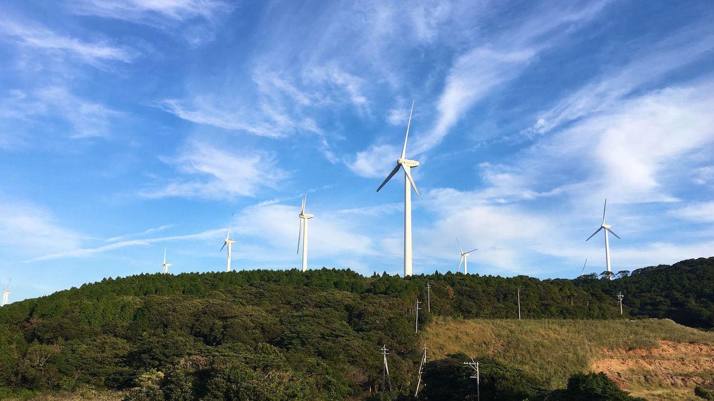 風力発電機が山頂にたくさん並んでいる