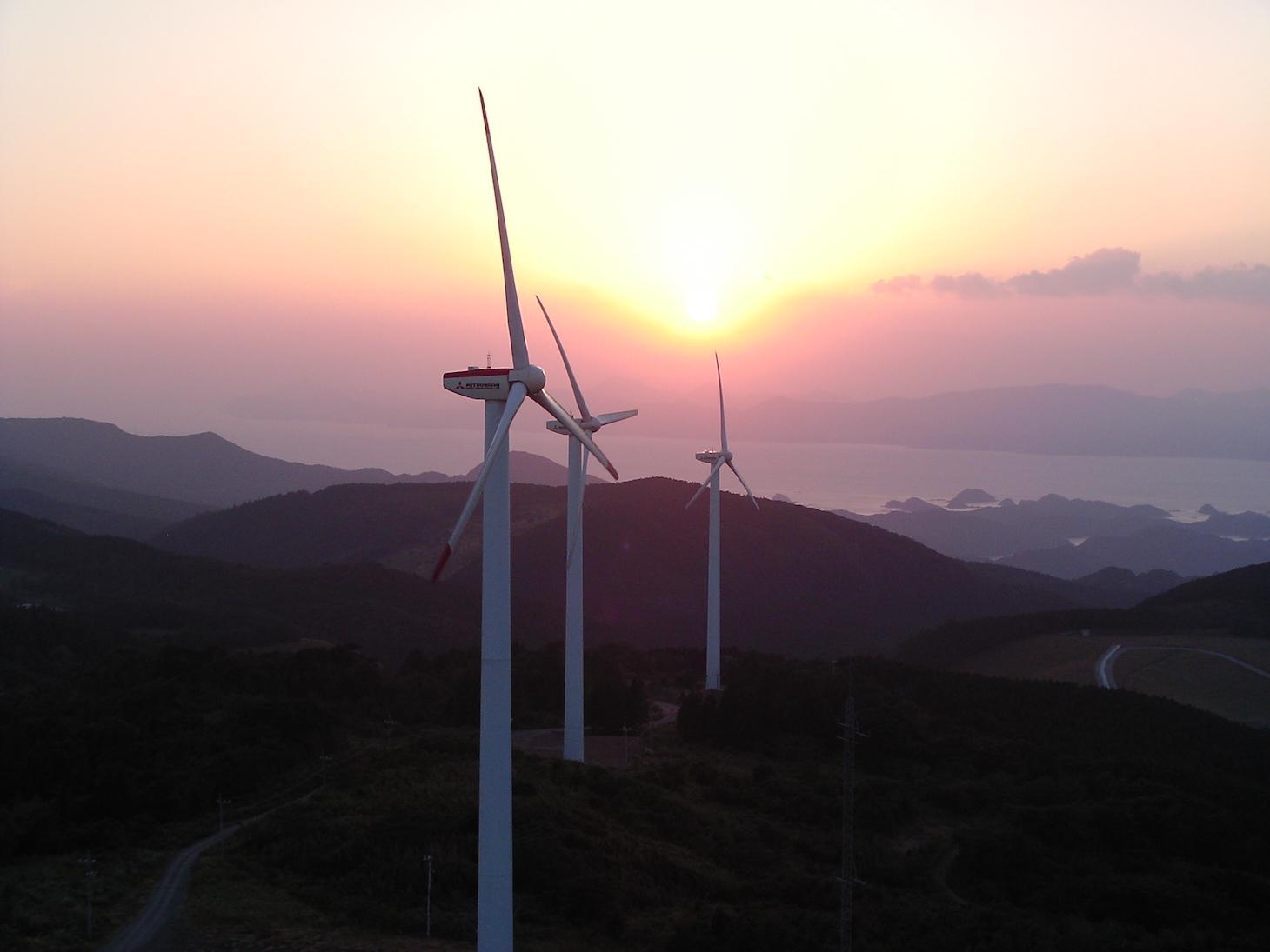 夕焼けをバックに空撮された風車発電機